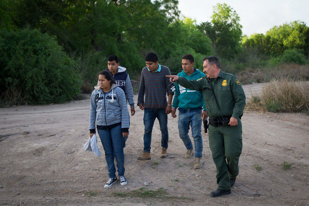 A Border Patrol agent apprehends immigrants shortly after they crossed the border from Mexico into the United States on Monday, March 26, 2018 in the Rio Grande Valley Sector near McAllen, Texas. An estimated 11 million undocumented immigrants live in the United States, many of them Mexicans or from other Latin American countries. / AFP PHOTO / LOREN ELLIOTT/AFP/Getty Images