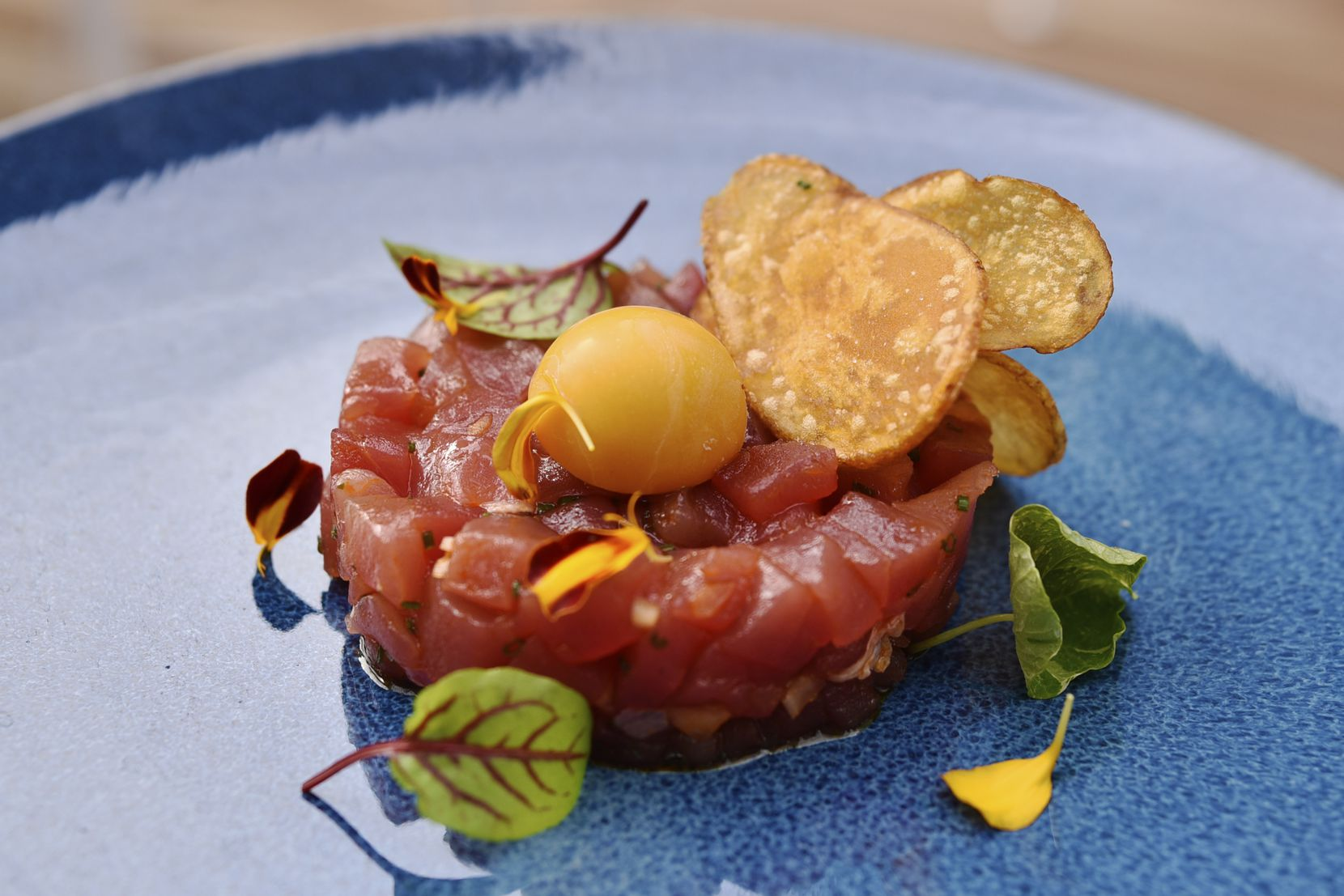 Tuna tartare, which is an appetizer, is served with radish, soy-lime vinaigrette and sea salt chips.
