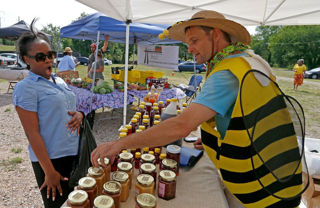 Brandon Pollard (right) talks with Natalie Steward about honey products at Texas Honeybee Guild's booth at the farmers market on the Paul Quinn College campus.