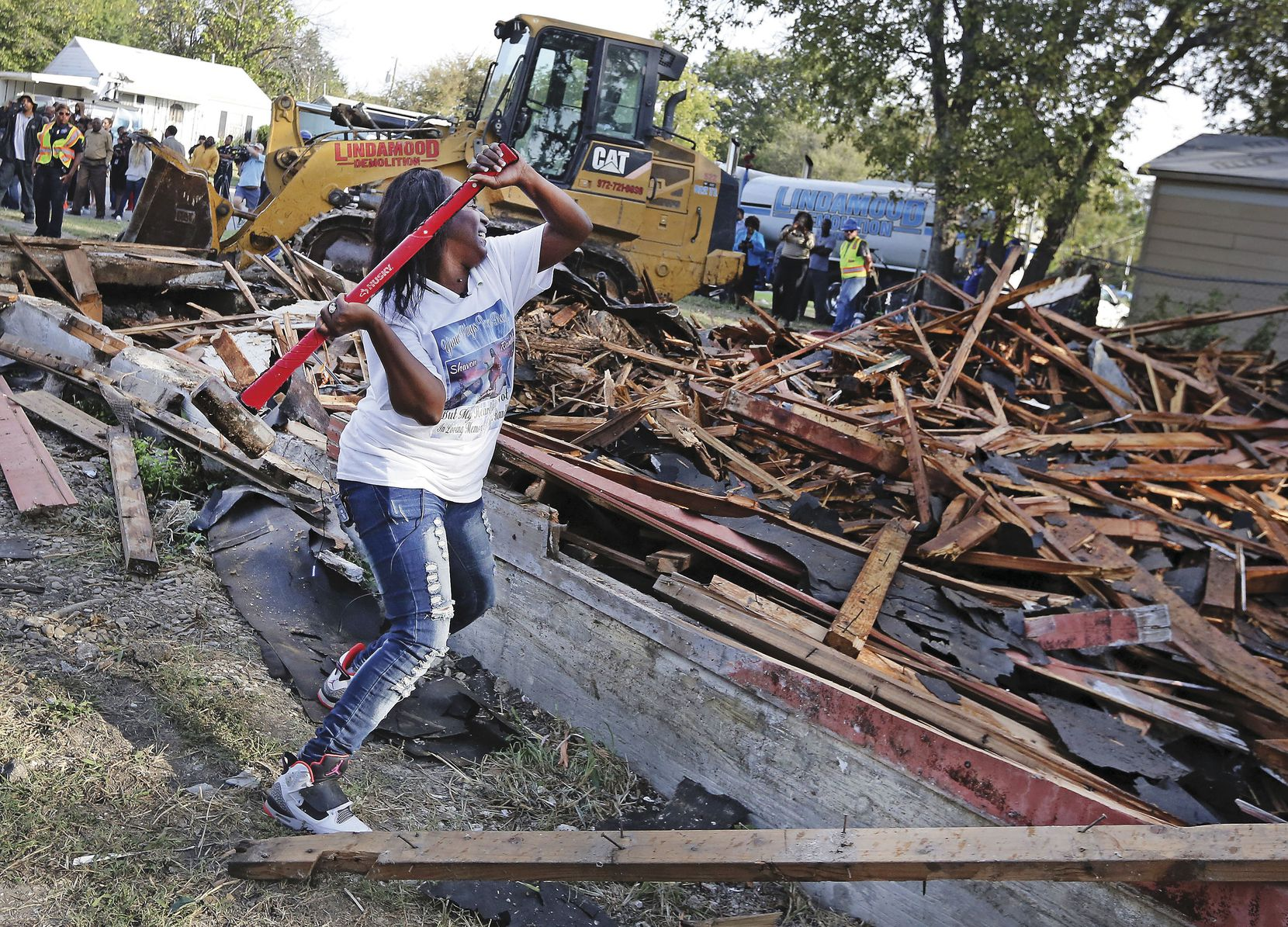 "Cynthia King, Shavon Randle's great-aunt, puts the finishing whacks on ""this godforsaken house"" where the girl's body was found. Relatives and neighbors gathered for the demolition of the run-down structure on Kiest Boulevard in October."