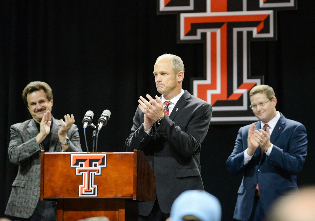 Texas Tech's new head football coach Matt Wells, center receives a standing ovation from Kirby Hocutt, Lawrence Schovanec and the crowd during the introductory news conference Saturday, Dec. 1, 2018, in Lubbock, Texas. (Abbie Burnett/Lubbock Avalanche-Journal via AP)