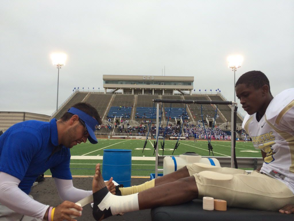 Conrad High School athletic trainer Kirk Kaps tapes the ankle of freshman Carlos Griffin (9)  before a high school football game at Standridge Stadium in Carrollton on Friday, Sept. 12, 2014.