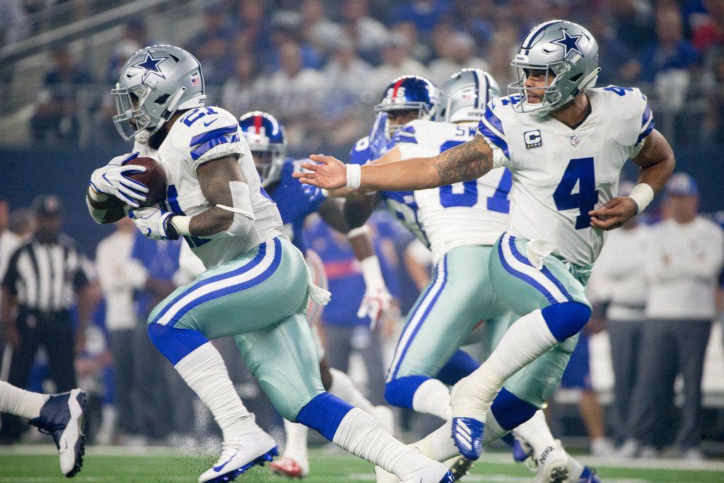 Dallas Cowboys quarterback Dak Prescott (4) hands the ball off to Dallas Cowboys running back Ezekiel Elliott (21) during an NFL game between the Dallas Cowboys and New York Giants on Sunday, September 16, 2018 at AT&T Stadium in Arlington, Texas.