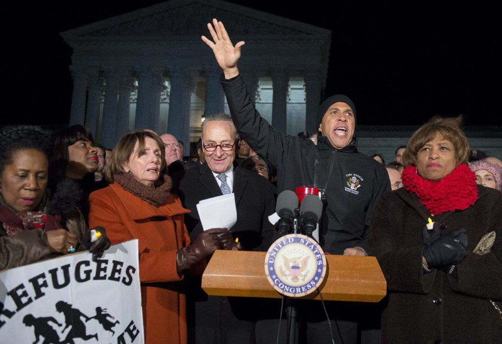 US Senator Cory Booker (2nd R), Democrat of New Jersey, speaks alongside Senate Minority Leader Chuck Schumer (C), Democrat of New York, US House Democratic Leader Nancy Pelosi (2nd L) and other members of Congress as demonstrators protest against US President Donald Trump and his administration's ban of travelers from 7 countries by Executive Order, during a rally outside the US Supreme Court in Washington, DC, on January 30, 2017. Trump's executive order suspended the arrival of all refugees for at least 120 days, Syrian refugees indefinitely -- and bars citizens from Iran, Iraq, Libya, Somalia, Sudan, Syria and Yemen for 90 days.  Protests are taking place at airports across the country in opposition to the ban. / AFP PHOTO / SAUL LOEBSAUL LOEB/AFP/Getty Images