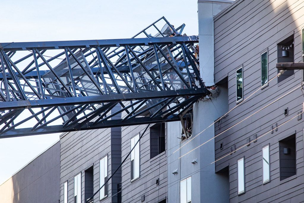 A crane remains embedded in the Elan City Lights apartment complex in Dallas on Friday. The crane fell during a major storm last month on June 9.