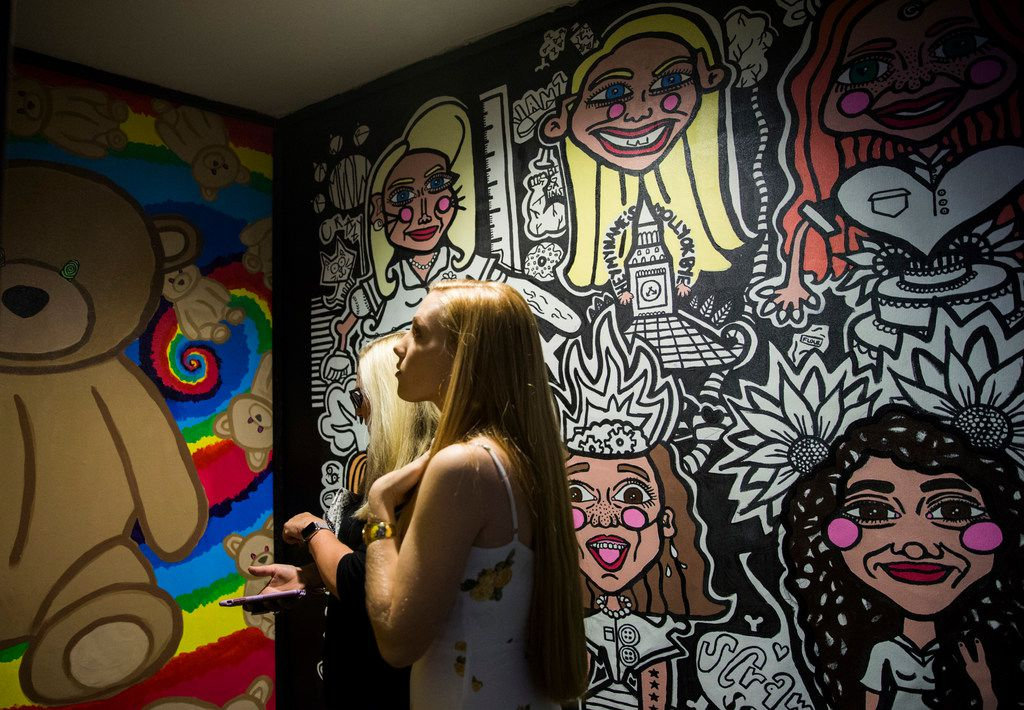 Women look at artwork inside a new pop-up art installation called Psychedelic Robot in Dallas.