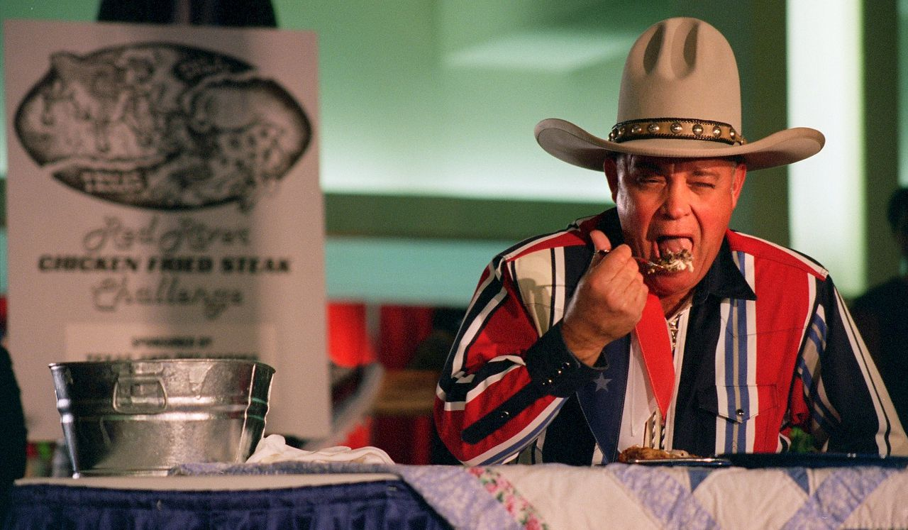"""John Lyon, """"Big Tex,"""" takes a  mouthful at the Red River chicken fried steak challenge in 1996. Texas beat competitors from Oklahoma."""