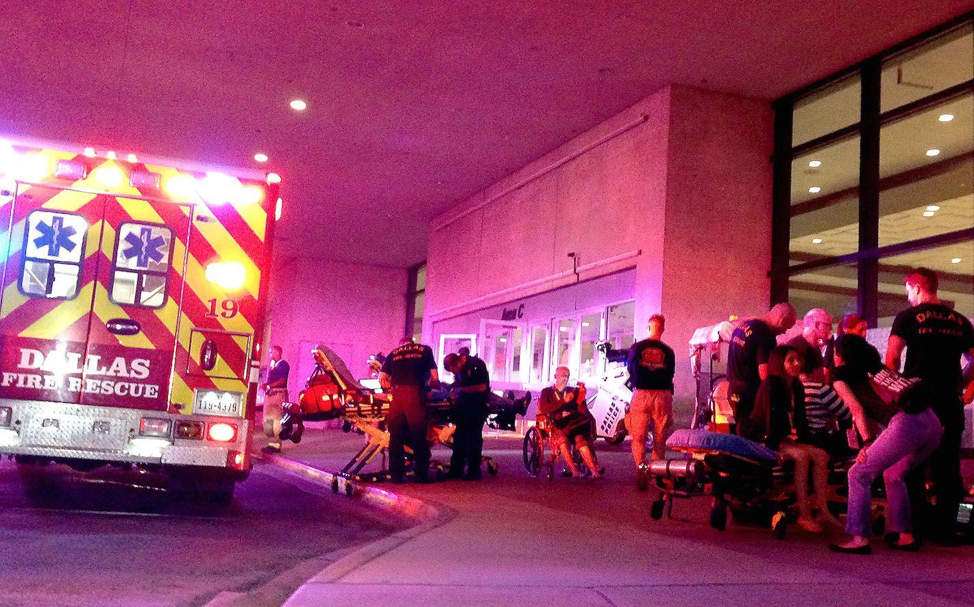 Paramédicos atienden a personas que se quemaron sus pies al intentar caminar sobre carbones encendidos en el Centro de Comunicaciones de Dallas.