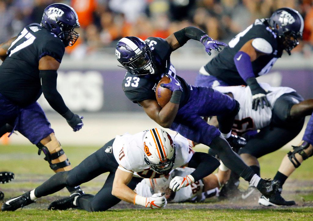TCU Horned Frogs running back Sewo Olonilua (33) has his feet taken out from under him by Oklahoma State Cowboys defensive end Brock Martin (40) during the third quarter at Amon G. Carter Stadium in Fort Worth, Texas, Saturday, November 24, 2018. The Frogs hung onto win, 31-24. (Tom Fox/The Dallas Morning News)