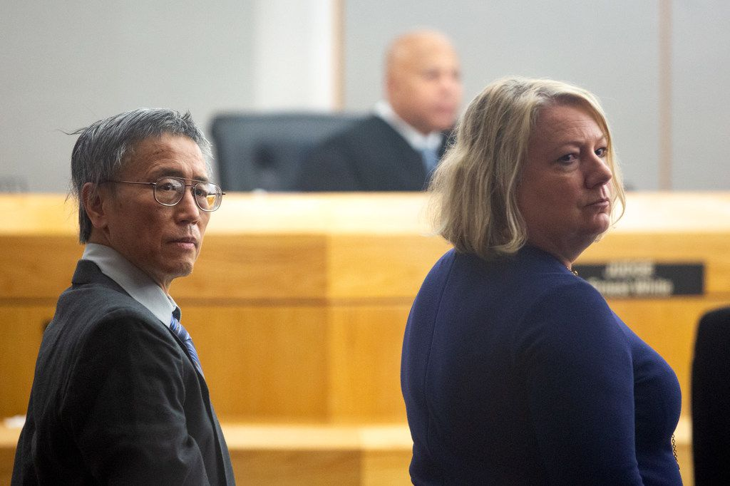 Former doctor George Guo stands with his defense lawyers during his capital murder trial Monday.
