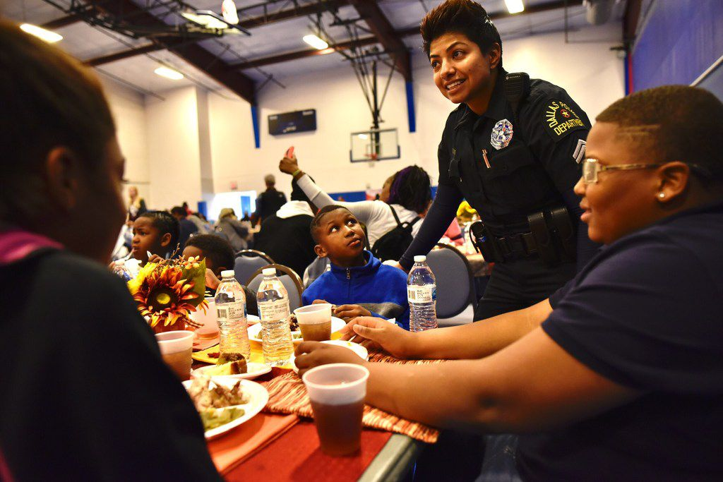 Police Officer Amber Roman visits with Jeremiah Robinson (left), 8, and Jaylen Massington, 12, as they eat Thanksgiving lunch during the St. Philips School and Community Center's Thanksgiving Feast with the community in Dallas.