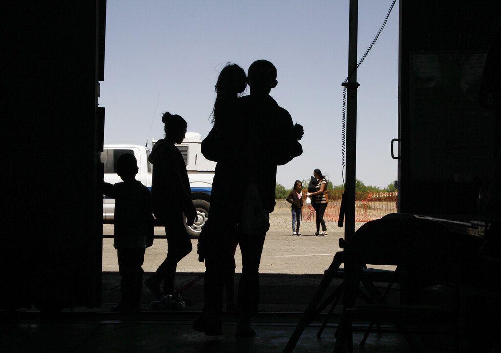 ARCHIVO – Esta foto de archivo del miércoles 22 de mayo del 2019 muestra a migrantes, mayormente de Centroamérica, en un hangar en Deming, Nuevo México. (AP Foto/Cedar Attanasio, Archivo)