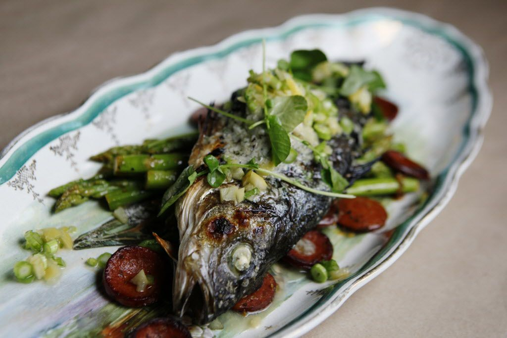 Slate rock-roasted whole grilled fish with anchovy butter, preserved lemon,  sausage and asparagus