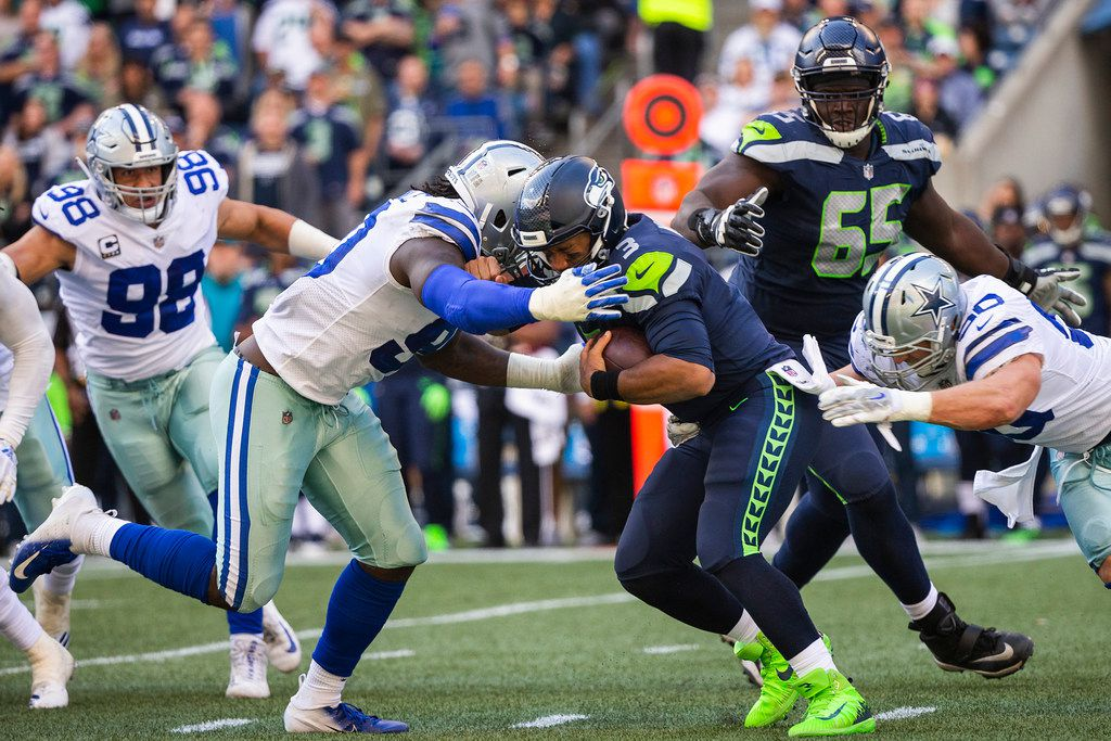 FILE - Seahawks quarterback Russell Wilson (3) is sacked by Cowboys defenders DeMarcus Lawrence (90) and Sean Lee (50) during the second half of a game at CenturyLink Field on Sunday, Sept. 23, 2018, in Seattle. (Smiley N. Pool/The Dallas Morning News)