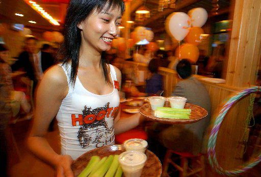 ORG XMIT: *S0410620909* A Chinese waitress brings dish during the pre-opening of Hooters  Friday Oct. 22, 2004 in Shanghai, China. Hooters, the Atlanta-based operator and franchiser, will open its first- restaurant in the mainland China on Oct. 24th. (AP Photo/Eugene Hoshiko) SHA106 10232004xBiz 11292004xQUICK