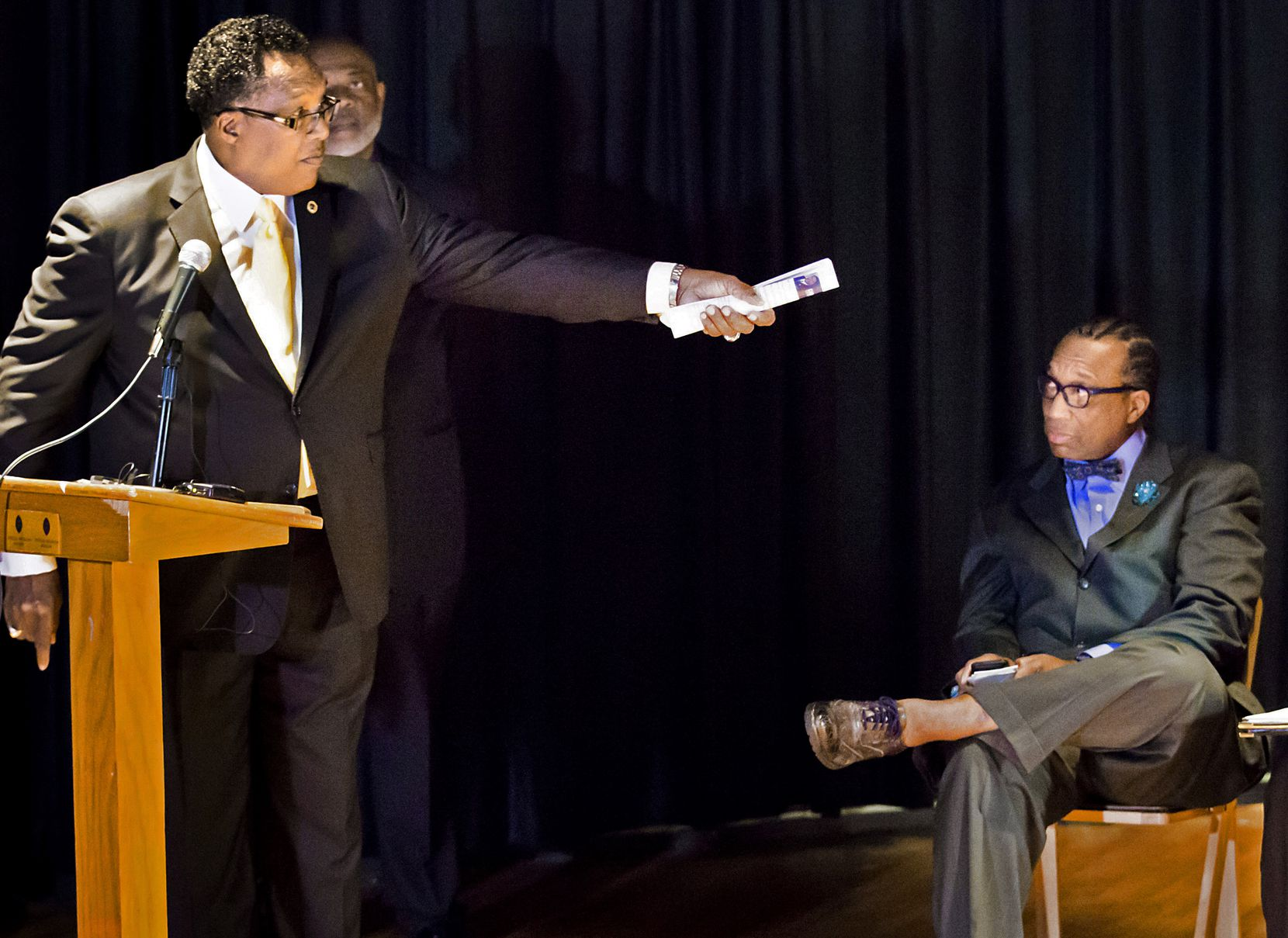 Dwaine Caraway (left) motions to incumbent John Wiley Price as Democratic primary candidates for Dallas County District 3 commissioner participate in a February 2016 candidate forum at the African American Museum in Fair Park.