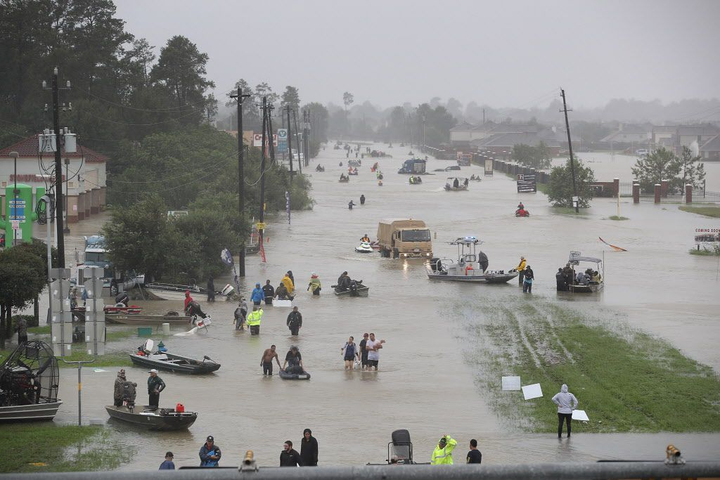 People walk down a flooded street as they evacuate their homes after the area was inundated with flooding from Hurricane Harvey Aug. 28 in Houston.