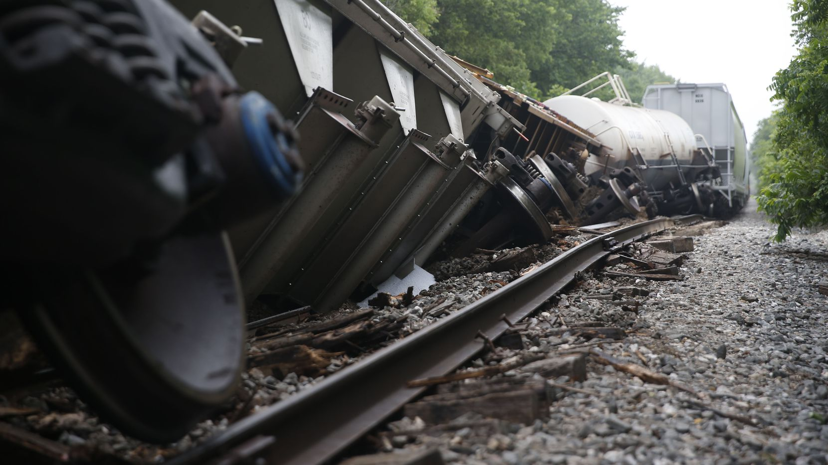 Cars lie tilted off the tracks Wednesday morning after a train derailment Monday night on the railroad line traveling through the Tenison Park Golf Course near the 3600 block of Samuell Boulevard, on the east side of Dallas.