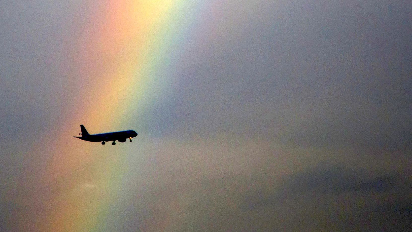 An American Airlines flight passes in front of partial rainbow on approach to landing at Dallas/Fort Worth International Airport on Tuesday, Oct. 3, 2017.