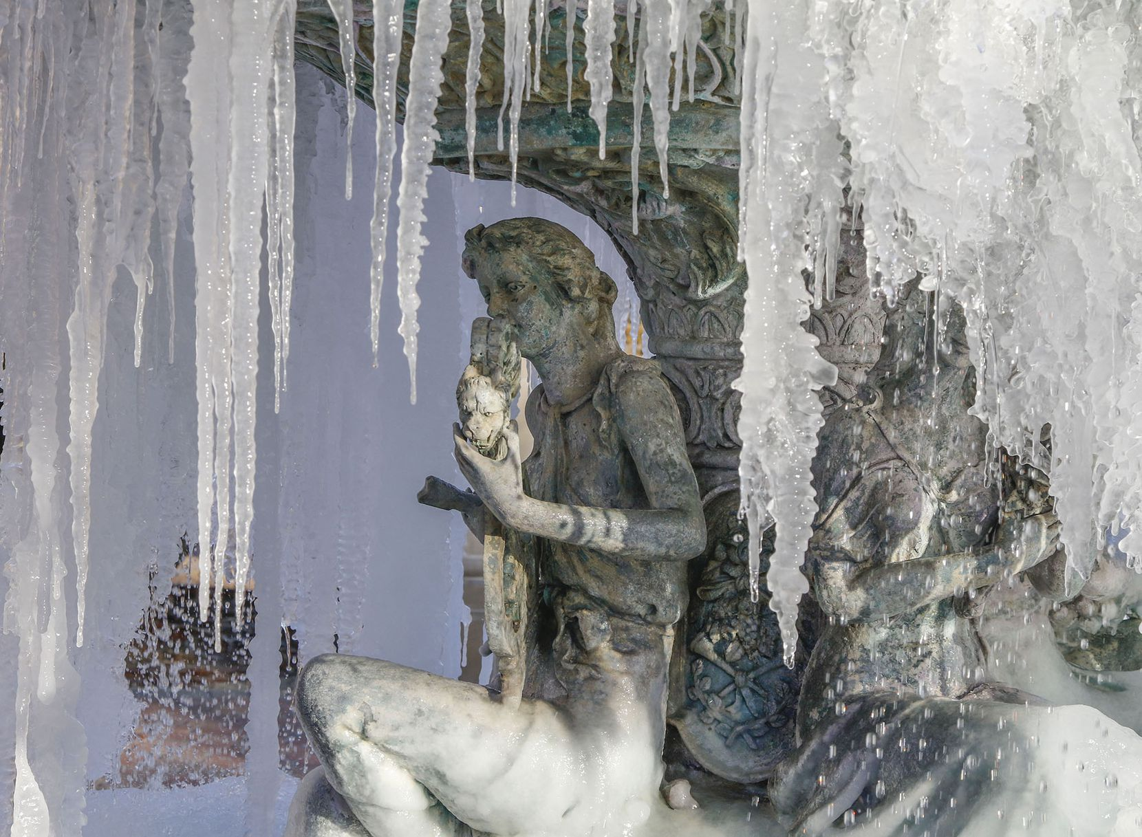 Icicles hang from a fountain at the The Village at Sports Center shopping center in Arlington on Monday.