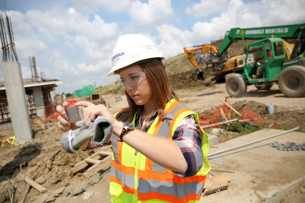 Amanda Calvert, an intern with Skanska construction, takes a photo of the construction progress while walking the perimeter of the job site she is working on, The Music Factory in Irving.