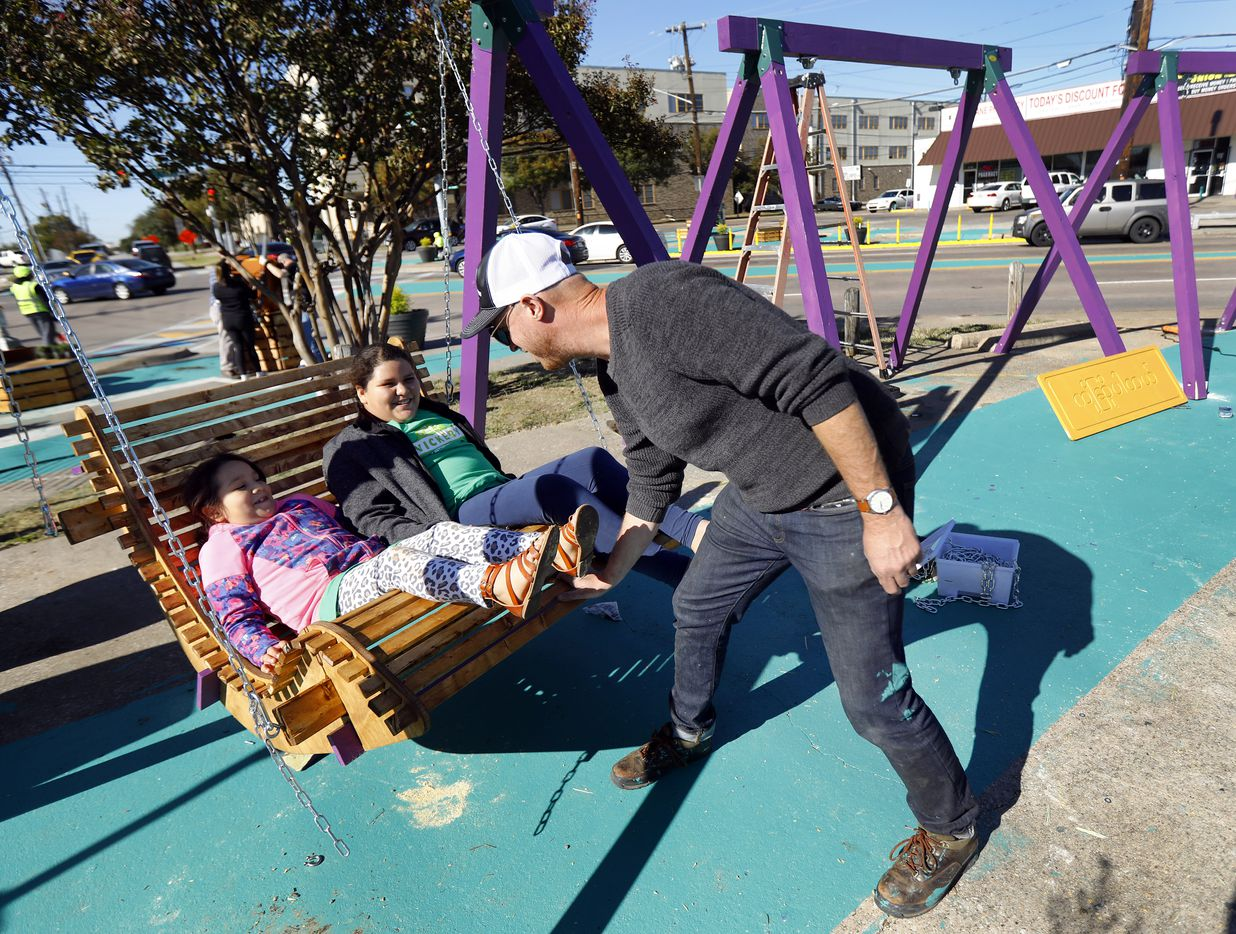 Better Block founding director Jason Roberts use students Yaretci Hernandez (left) and sister Kayli Hernandez to test a newly constructed swing at the Five Points street intersection in the Vickery Meadow area of Dallas, Friday, November 1, 2019. Improvements include adding a plaza, potted trees a pop-up container store, stage, swings and colorful walkways to beautify the neighborhood. The goal is to reduce crime through improving the environment.
