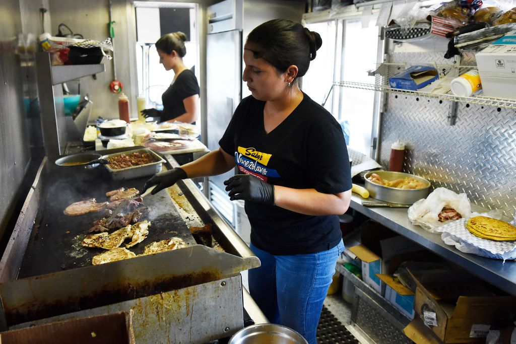 Co-owner Dariela Cuadrado, of Sabor Venezolano Express, cooks meat inside her food truck parked in Carrollton.