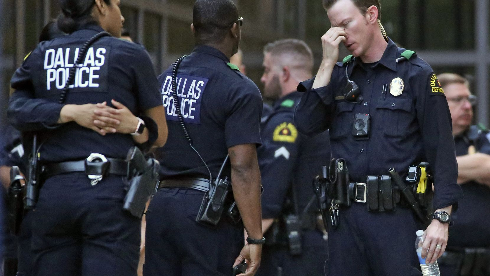 Dallas Police officers wait outside the entrance of the emergency room at Presbyterian Hospital, Tuesday, April 24, 2018, in Dallas, following a shooting at an area Home Depot where two police officers and a civilian were shot. The officers were critically wounded in the shooting, according to officials. (Louis DeLuca/The Dallas Morning News via AP)