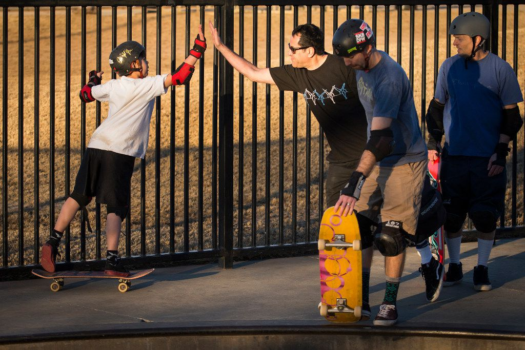 Travis Haley, 9, high-fives Richard Iniguez as Clinton Haley prepares to drop into the bowl for a skateboard run at Lively Pointe Skate Park on Sunday, Jan. 22, 2017, in Irving. (Smiley N. Pool/The Dallas Morning News)