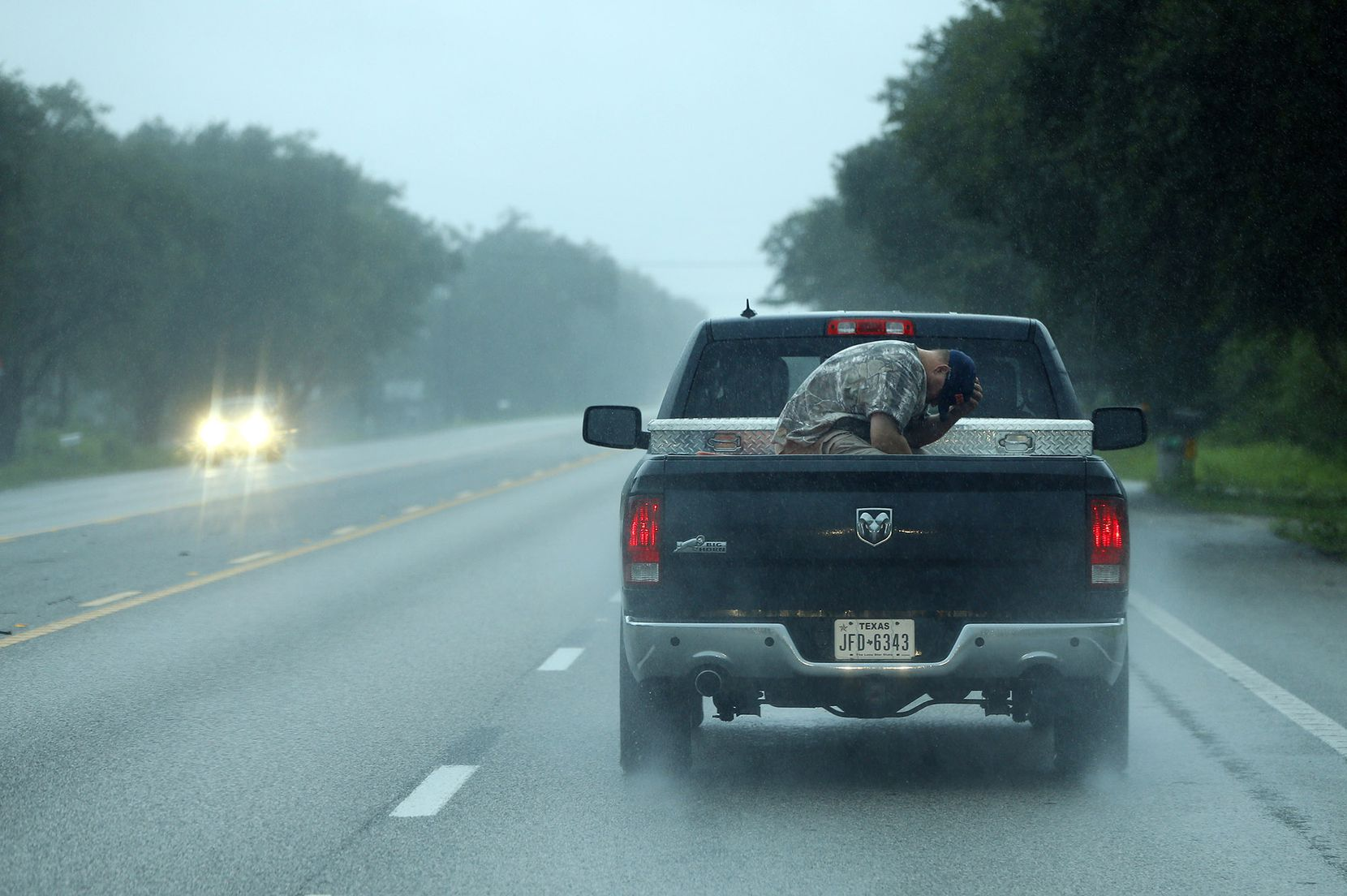 A man shield his face from the wind and rain as he gets a ride in the bed of a pickup in Santa Fe, Texas, Monday, August 28, 2017, after Tropical Storm Harvey dumped feet of rain on the Houston area.