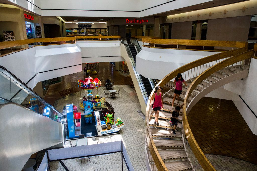 Children walk down a staircase inside Southwest Center Mall, which will undergo major renovations and be renamed Redbird Mall.