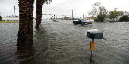 Dos vehículos cruzan una zona inundada tras el paso del huracán Harvey el sábado 26 de agosto de 2017, en Aransas Pass, Texas. Foto AP