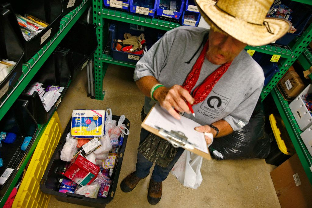 Volunteer James LaBonte picks out items for the homeless next to a box of feminine hygiene products at Our Calling in Dallas.  (Nathan Hunsinger/Staff Photographer)