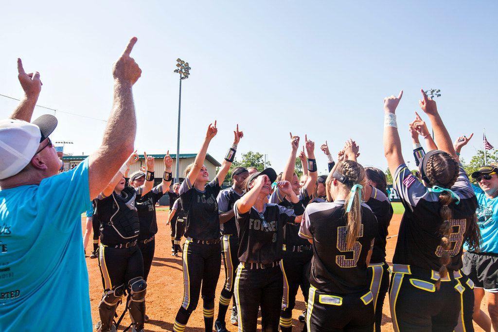 Forney coach Pat Eitel and his players point to the sky to remember Emily Galiano after beating Richmond Foster to win the Class 5A softball state championship last season. (Thao Nguyen/Special Contributor)