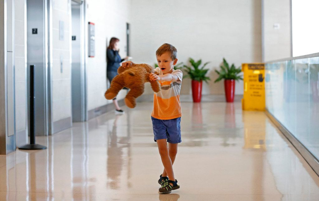 """Luke Swofford, 4, plays with his teddy bear named """"Teddy Bear"""" in the hallway after he picks him up at the lost and found at Dallas Love Field Airport in Dallas, Wednesday, July 26, 2017."""