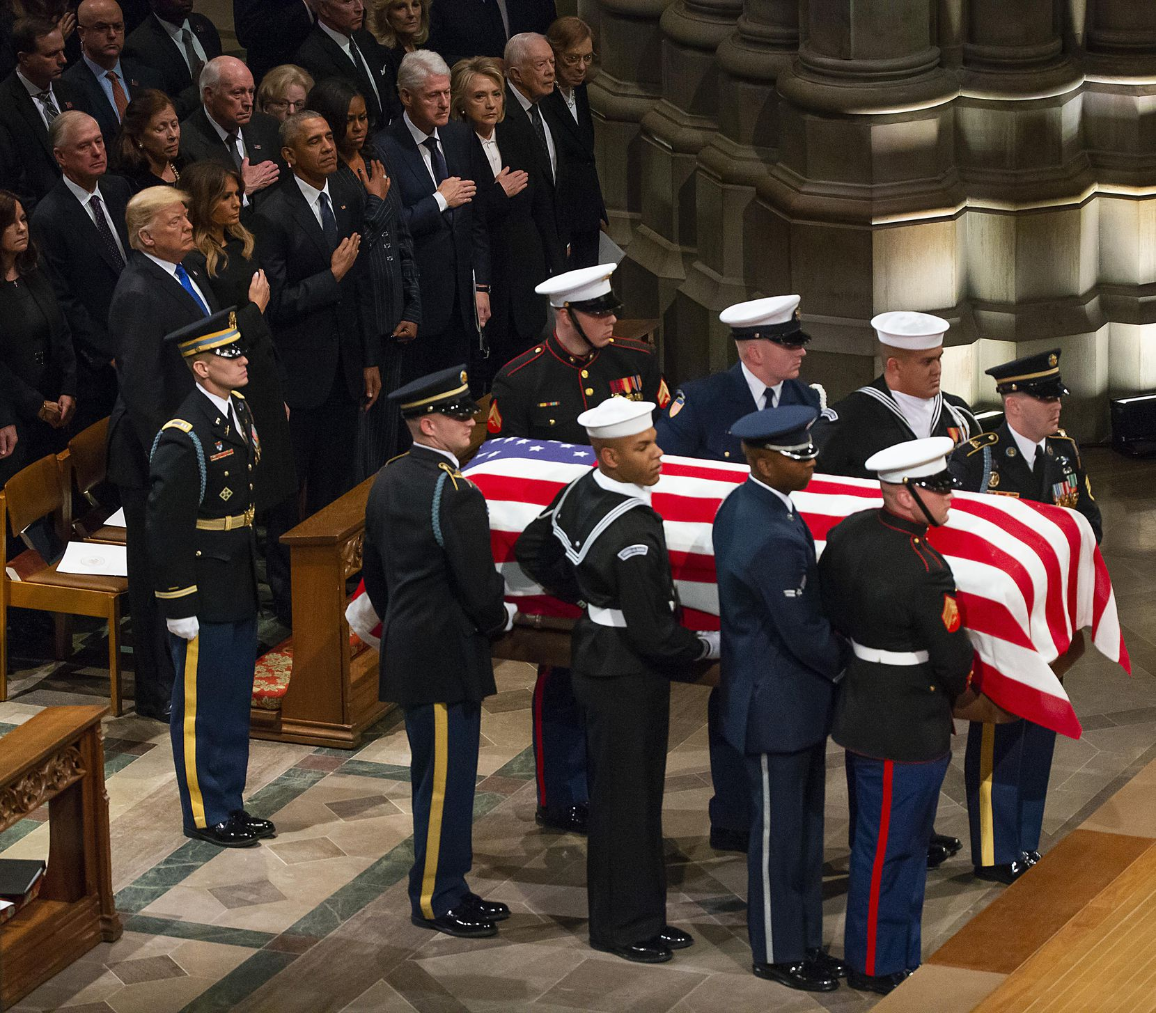 A military honor guard carries the flag-draped casket into the Washington National Cathedral past, from left, President Donald Trump, first lady Melania Trump, former President Barack Obama, Michelle Obama, former President Bill Clinton, former Secretary of State Hillary Clinton, former President Jimmy Carter, and Rosalynn Carter at the beginning of the State Funeral for George H.W. Bush, the 41st President of the United States, on Wednesday, Dec. 5, 2018, in Washington. (Smiley N. Pool/The Dallas Morning News)