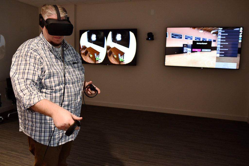 Aaron Tate, lead artist for the Brain Performance Institute, demonstrates how the virtual world computer program Charisma works during a tour of the Brain Performance Institute at the Center for Brain Health in Dallas.