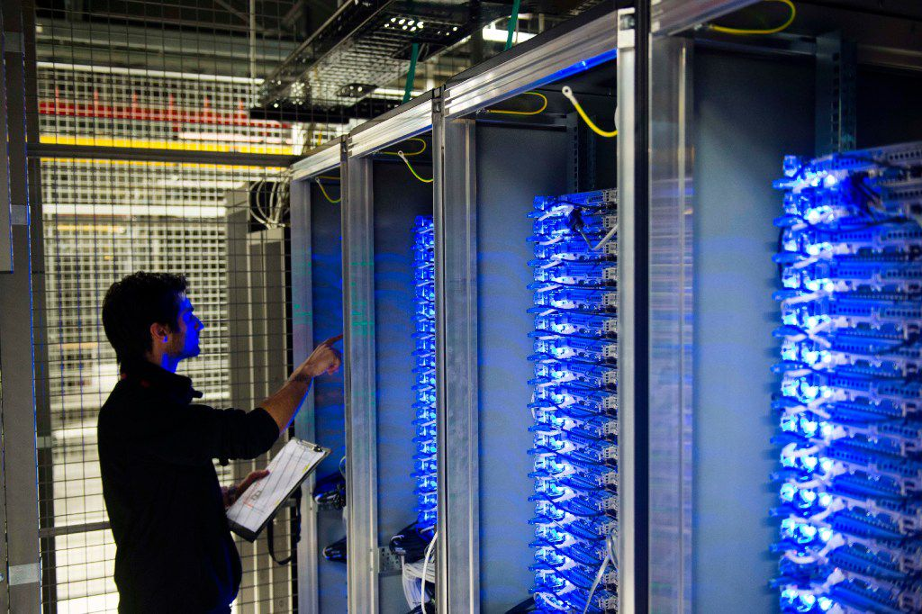 """(FILES) This file photo taken on July 21, 2014 shows an employee of Equinix data center checking servers on July 21, 2014 in Pantin, a suburb north of Paris in the Seine-Saint-Denis department.   The world's biggest ransomware attack levelled off in Europe on May 15, 2017 hanks to a pushback by cyber security officials after causing havoc in 150 countries, as Microsoft urged governments to heed the """"wake-up call"""". / AFP PHOTO / MARTIN BUREAUMARTIN BUREAU/AFP/Getty Images"""