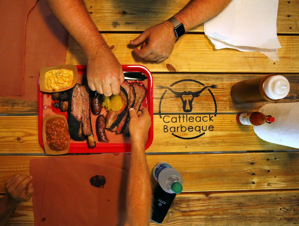 Diners dive into a tray full of burnt ends, brisket, beef rib, Texan spicy sausage, Italian sausage, with burnt ends beans and mac & cheese. Owners Todd and Misty David reopened CattleAck BBQ, Wednesday, July 7, 2016, after doubling the size of their location at 13628 Gamma Rd. in North Dallas. (Tom Fox/The Dallas Morning News)