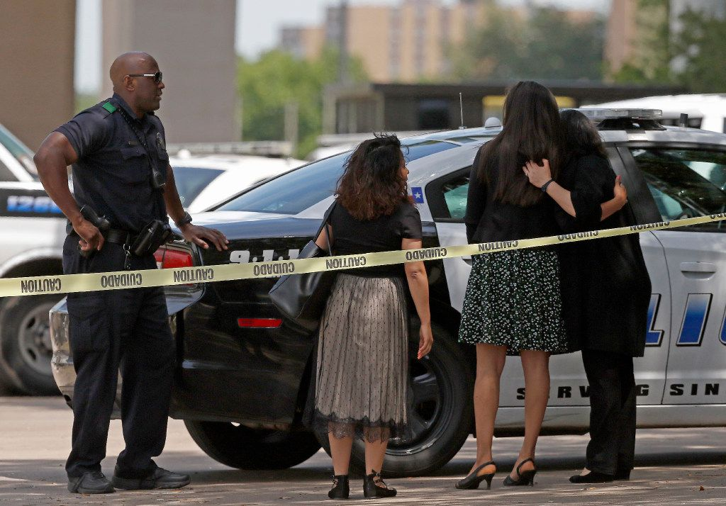 A Dallas Police Department officer (left) watches workers who evacuated a shooting scene where police found two people dead at an office building in Lake Highlands near the High Five in Dallas, Monday, April 24, 2017. (Jae S. Lee/The Dallas Morning News)