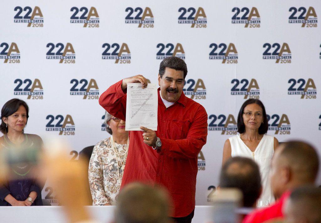 El presidente venezolano Nicolás Maduro presenta un certificado que formaliza su candidatura para las próximas elecciones presidenciales en el Consejo Nacional Electoral (CNE) en Caracas, Venezuela, el martes 27 de febrero de 2018. / AP