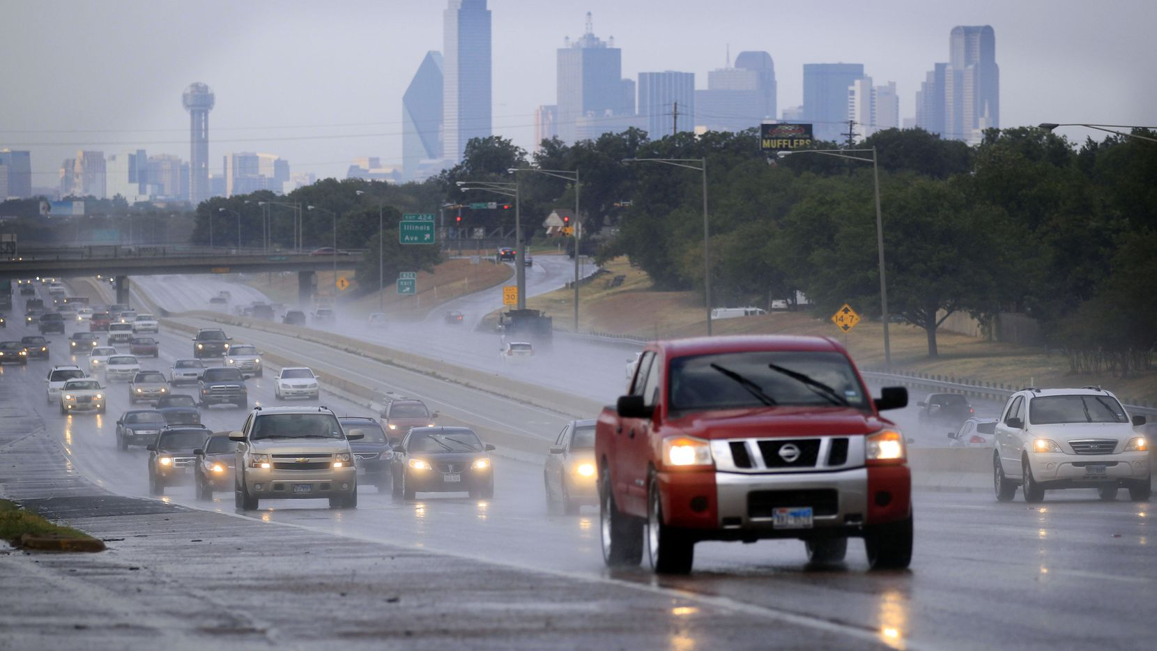 Drivers navigate Interstate 35W south of downtown Dallas during a light rain.