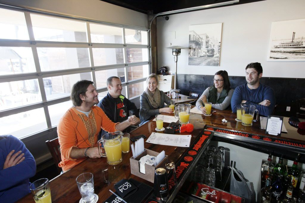 Chaps Tucker, 30, left, wearing a onesie, sits at the bar with friends drinking mimosa pitchers during brunch at 504 Bar and Grill, on Sunday, Jan. 10, 2016 on Greenville Avenue in Dallas.