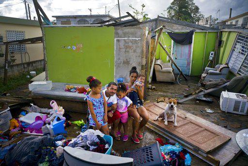 En esta fotografía del sábado 14 de octubre de 2017, Arden Dragoni, segundo de izquierda a derecha, posa con su esposa Sindy, sus tres hijos y su perro Max, rodeados por lo que queda de su vivienda destruida por el huracán María en Toa Baja, Puerto Rico. La familia Dragoni ha estado viviendo en un albergue establecido en una escuela desde que el meteoro destruyó su casa de madera a fines de septiembre. Perdieron todo: ropa, bienes del hogar, y un viejo automóvil. Dragoni mantenía a su familia como trabajador de la construcción, pero por el momento sus empleadores no tienen trabajo, lo que lo deja a él y a su familia sin una fuente de ingresos. (AP Foto/Ramón Espinosa)