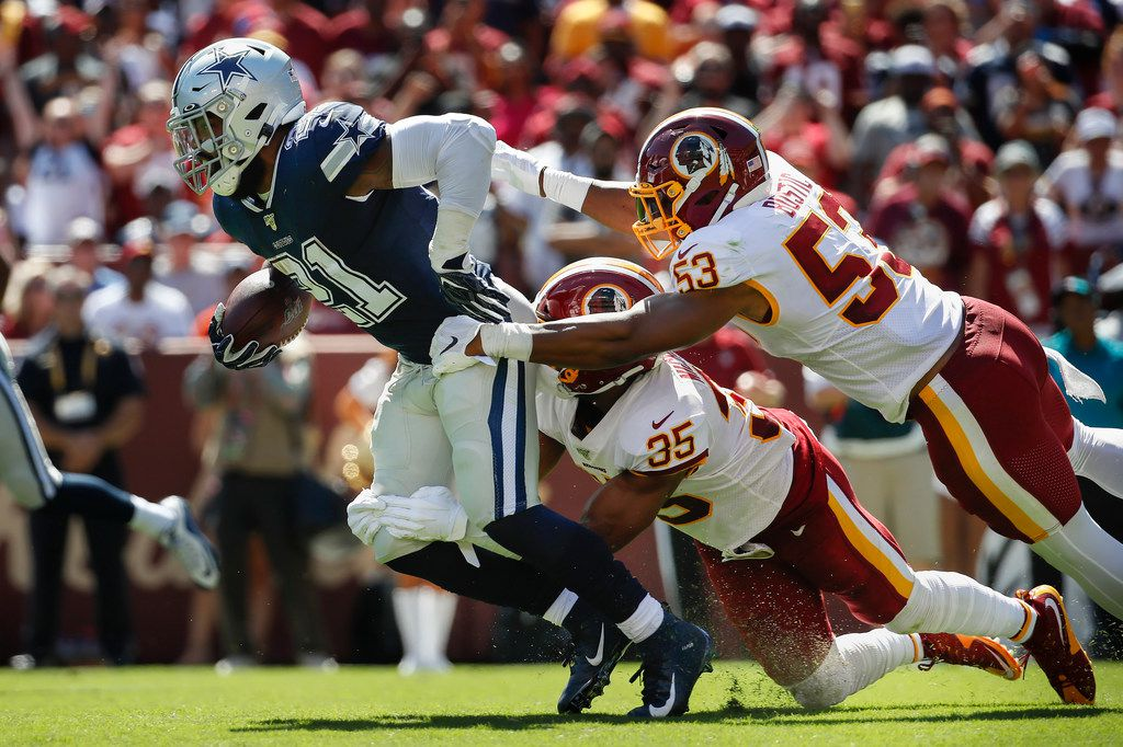 Dallas Cowboys running back Ezekiel Elliott (21) is taken down by Washington Redskins strong safety Montae Nicholson (35) and inside linebacker Jon Bostic (53)in the first half of an NFL football game, Sunday, Sept. 15, 2019, in Landover, Md.