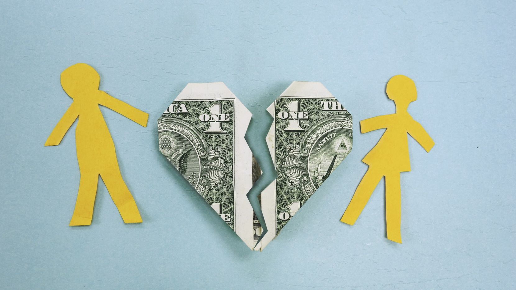Paper couple and broken dollar heart - divorce or money trouble concept