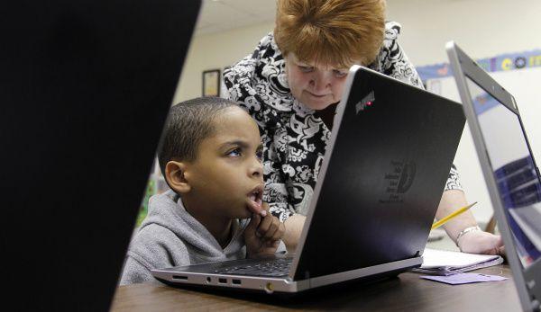 Erma Pruett, a second-grade teacher at Kleberg Elementary School, watched Jaelonn Cox solve math problems on a computer, part of the Reasoning Mind program at the school.