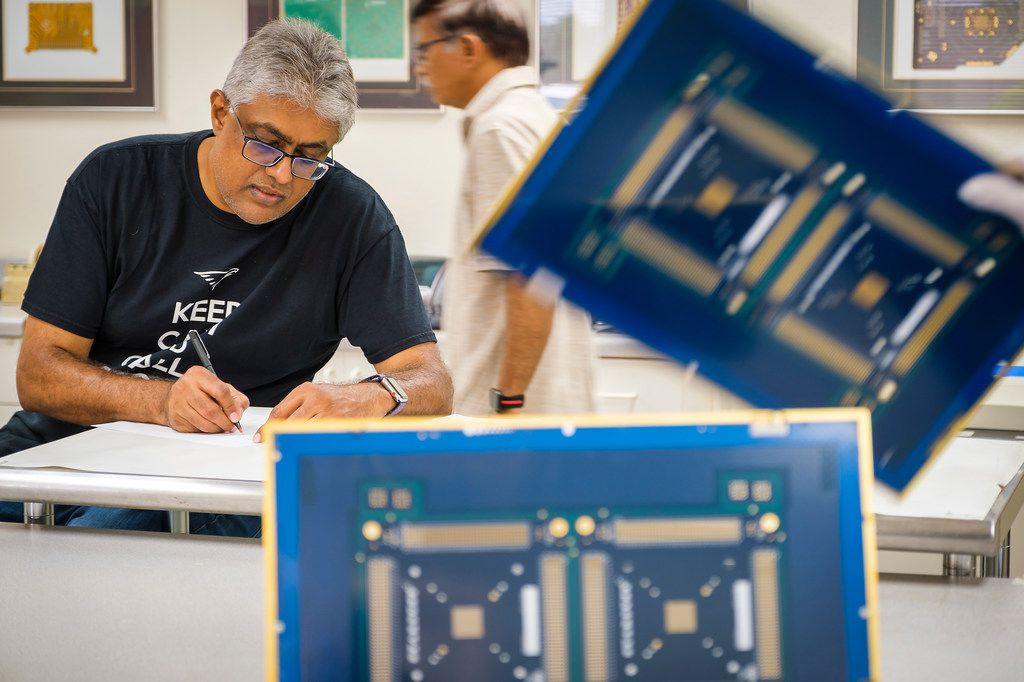 Nilesh Naik, CEO of Eagle Circuits, works with employees at the company's facility on Aug. 2, 2019, in Dallas.