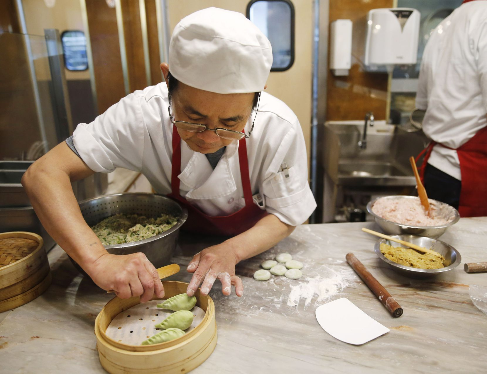 "Cheng-Hui ""Tony"" Lai prepares vegetable dumplings in a glassed-in station in the dining room."