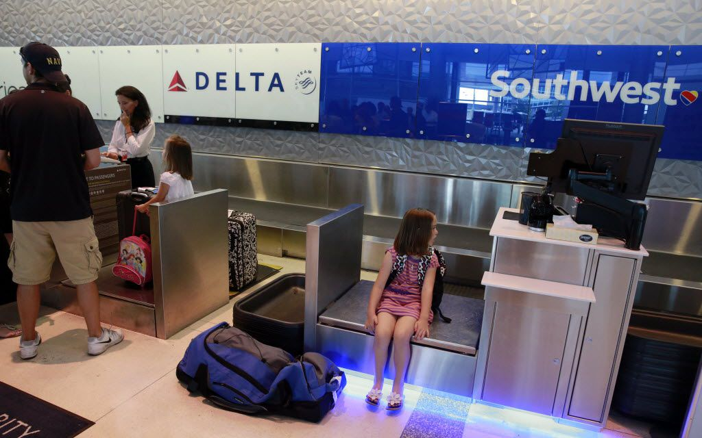 A young passenger waits on a Southwest Airlines scale as her family checks in at the adjacent Delta Air Lines desk at Dallas Love Field in Dallas on June 10, 2016.